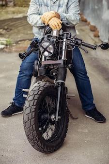 Schließen sie die vorderseite des motorradrads. der fahrer sitzt souverän auf einem motorrad, hält einen helm in den händen und ist fahrbereit.