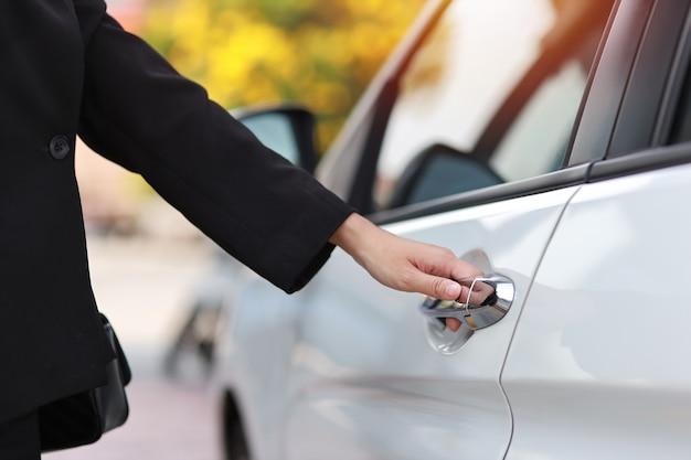 Schließen sie die weibliche hand des geschäfts, die auto- oder automobiltür öffnet