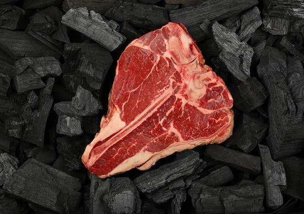 Schließen sie ein gealtertes, erstklassiges, marmoriertes rohes porterhouse-t-bone-beef-steak auf schwarzen holzkohlestücken, die zum grillen bereit sind, erhöhte draufsicht, direkt darüber