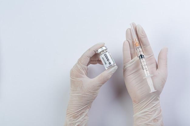 Schließen sie eine durchstechflasche mit einem covid-19-impfstoff in der hand eines wissenschaftlers oder arztes