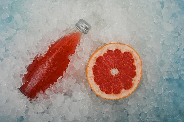 Schließen sie eine glasflasche mit kaltem rotem saftgetränk mit chiasamen und halb geschnittener rosa grapefruit auf crushed ice direkt darüber