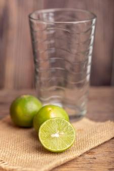 Schließen sie eine hälfte des grünen limettenplatzes auf dem geflochtenen sack und dem verschobenen leeren glas in einer küche
