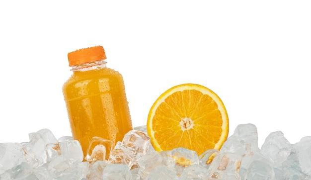 Schließen sie eine plastikflasche mit frischem orangensaft und schneiden sie eine halbe orangenscheibe auf eiswürfeln, die auf einer weißen seitenansicht mit niedrigem winkel isoliert sind