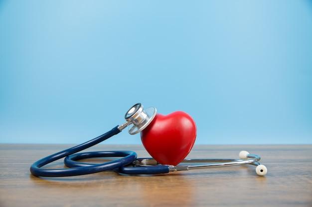 Schließen sie eine rote herzform und ein medizinisches stethoskop.