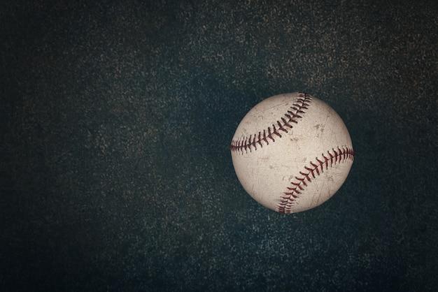Schließen sie einen alten abgenutzten vintage-baseballball mit rotem stich auf dunkelbraunem grunge-hintergrund mit kopierraum, erhöhter draufsicht, direkt darüber