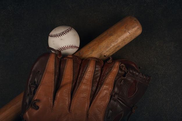 Schließen sie einen alten baseballball, einen holzschläger und einen abgenutzten vintage-lederhandschuh auf dunkelbraunem grunge-hintergrund, erhöhte draufsicht, direkt darüber