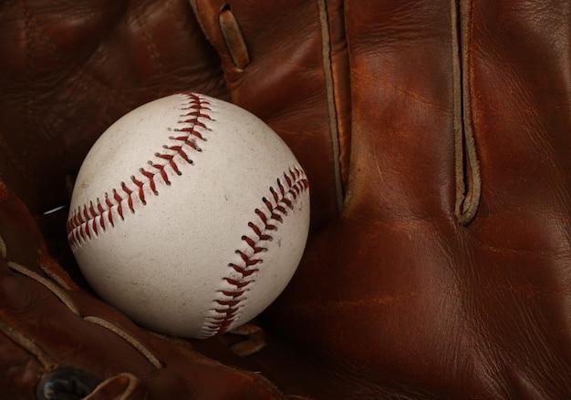 Schließen sie einen alten baseballball in einem abgenutzten braunen vintage-lederhandschuh, erhöhte ansicht