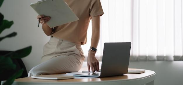 Schließen sie einen buchhalter, der mit taschenrechner und laptop im büro über finanzen arbeitet, um ausgaben zu berechnen, buchhaltungskonzept.