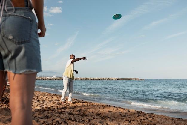 Schließen sie freunde, die am strand spielen Kostenlose Fotos