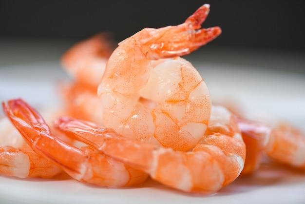 Schließen sie frische garnelen, die auf teller serviert werden - gekochte geschälte garnelengarnelen, die im fischrestaurant gekocht werden