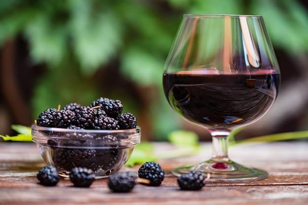 Schließen sie frische maulbeerfrüchte in der schüssel und wein im glas