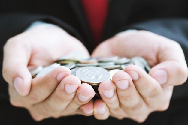 Schließen sie geldmünzen in händen