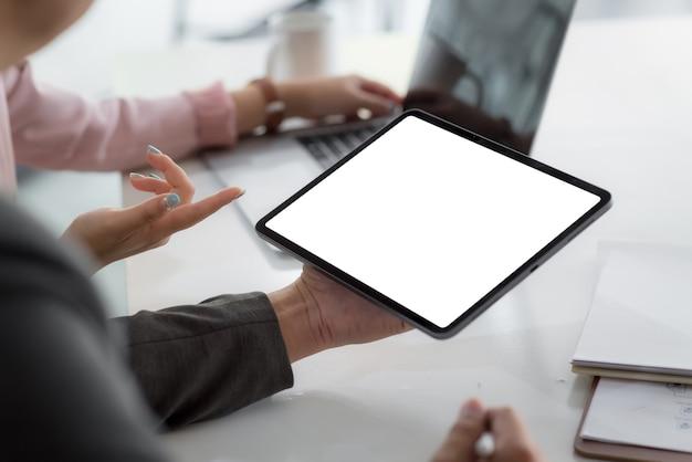Schließen sie geschäftsleute, die einen leeren weißen bildschirm des tablets im konferenzraum halten.