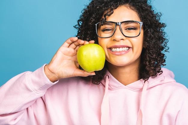 Schließen sie herauf afroamerikanische junge frau, die gesundes zahniges lächeln demonstriert, grünen apfel hält, zufriedener kundenkunde, der zahnaufhellungsservice, mundhygiene und behandlung empfiehlt