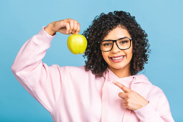 Schließen sie herauf afroamerikanische junge frau, die gesundes zahniges lächeln demonstriert, grünen apfel hält, zufriedener kundenkunde empfiehlt zahnaufhellungsservice, mundhygiene und behandlung