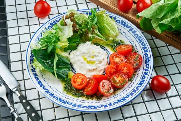 Schließen sie herauf ansicht auf appetitlichem salat mit italienischem strachatella-käse, salat, kirschtomaten in der schönen blauen keramikplatte auf weißem tisch. leckeres essen. flach liegen