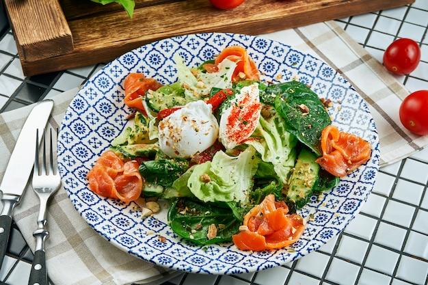 Schließen sie herauf ansicht auf appetitlichem salat mit lachs, spinat, pochiertem ei und ricotta in der schönen blauen keramikplatte auf weißem tisch. leckeres essen. flach liegen