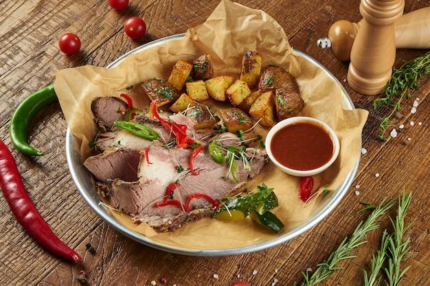 Schließen sie herauf ansicht auf barbecue schweinebauch mit chili-pfeffer und ofenkartoffeln auf pergament in einer zusammensetzung mit gewürzen auf einer holzoberfläche