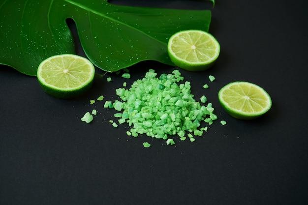 Schließen sie herauf ansicht auf grünem aromatischem badesalz mit tropischem blatt und limette auf einem schwarzen hintergrund mit kopienraum.