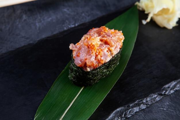 Schließen sie herauf ansicht auf gunkan-sushi mit würziger soße und thunfisch auf dunklem steinhintergrund. frische japanische küche. asiatisches essen.