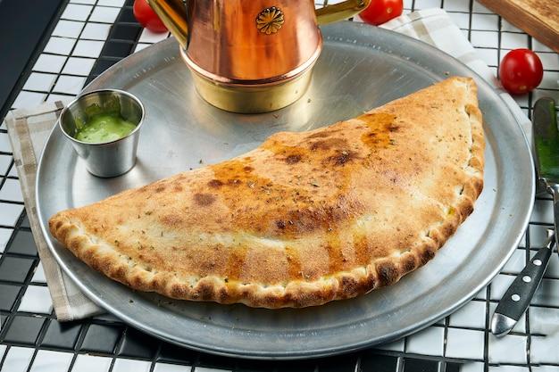 Schließen sie herauf ansicht auf hausgemachte und üppige calzone-pizza mit fleisch auf einem metalltablett und soße auf einem weißen tisch. leckeres essen zum mittagessen. flach liegen