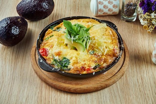 Schließen sie herauf ansicht auf hausgemachtes spanisches frittata-omelett mit spinat-, avocado- und kirschtomaten in einer schwarzen pfanne auf einem holztisch. spanische küche. leckeres mittagessen