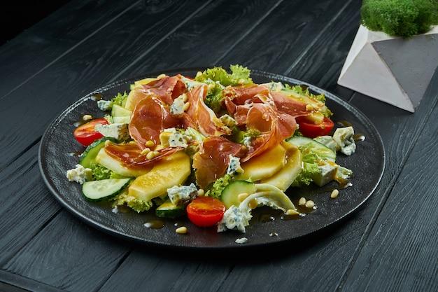 Schließen sie herauf ansicht auf salat mit honigbirne, blauschimmelkäse und schinken auf stilvollem dunklem teller auf schwarzem hölzernem hintergrund.