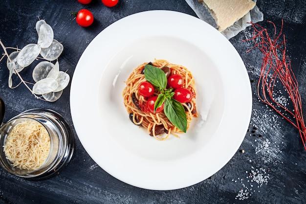Schließen sie herauf ansicht auf traditionelle italienische nudeln mit basilikum und kirschtomate im weißen teller. flache italienische küche mit kopierraum für design. mediterrane nudeln zum mittagessen. draufsicht