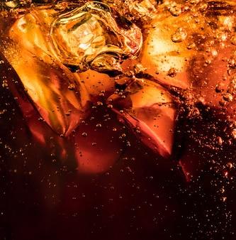 Schließen sie herauf ansicht der eiswürfel im dunklen cola-hintergrund. textur des kühlenden süßen sommergetränks mit schaum und makroblasen an der glaswand. zischen oder schweben bis zur oberfläche.