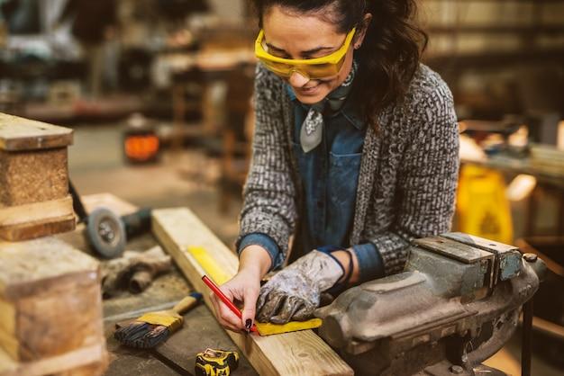 Schließen sie herauf ansicht der fleißigen fokussierten professionellen ernsthaften zimmermannsfrau, die lineal und bleistift hält, während markierungen auf dem holz am tisch in der stoffwerkstatt machen.