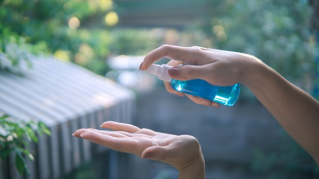 Schließen sie herauf ansicht der frau, die kleines tragbares antibakterielles händedesinfektionsmittel auf händen verwendet.