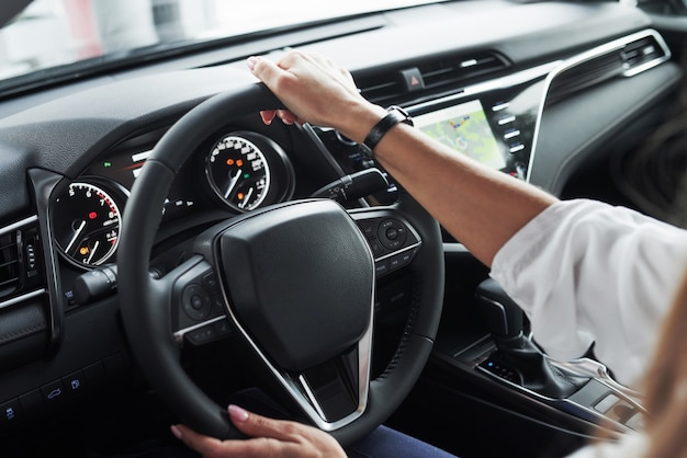 Schließen sie herauf ansicht der frauenhände in dem schönen modernen schwarzen farbigen auto