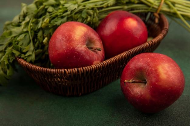 Schließen sie herauf ansicht der frischen roten äpfel und der petersilie auf einem eimer auf einer grünen oberfläche