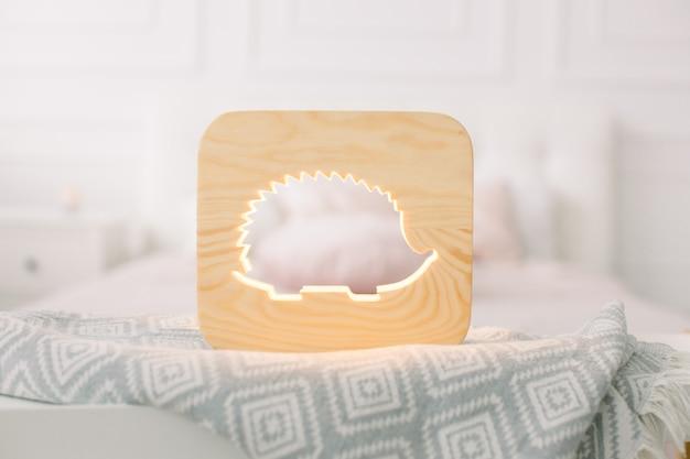 Schließen sie herauf ansicht der gemütlichen hölzernen nachtlampe mit igelausschnittbild, auf grauer decke am gemütlichen hellen schlafzimmerinnenraum