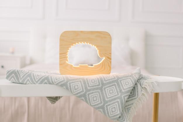Schließen sie herauf ansicht der gemütlichen hölzernen nachtlampe mit igelausschnittbild, auf grauer decke am gemütlichen hellen schlafzimmerinnenraum Premium Fotos