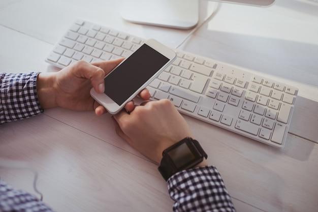 Schließen sie herauf ansicht der geschäftsfrau, die ihr telefon an ihrem schreibtisch im büro verwendet
