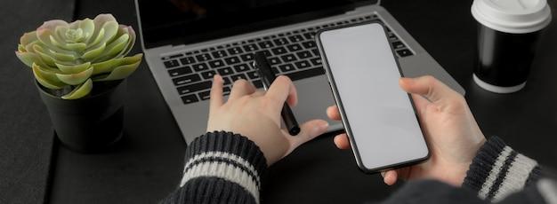 Schließen sie herauf ansicht der geschäftsfrau, die informationen auf smartphone auf schwarzem tisch sucht