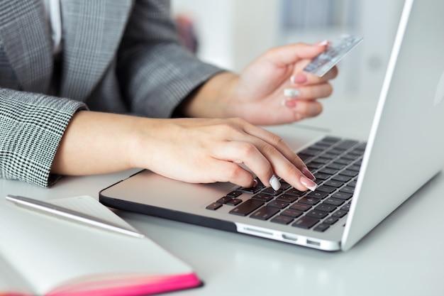Schließen sie herauf ansicht der geschäftsfrau hände, die kreditkarte halten und online-kauf mit notebook-pc machen