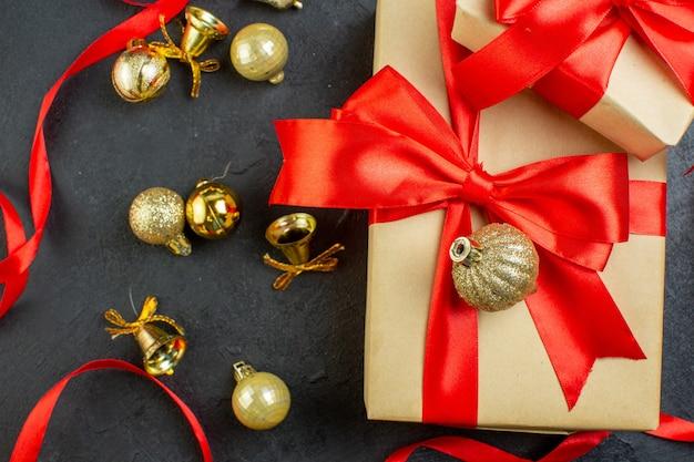 Schließen sie herauf ansicht der geschenkbox mit rotem band und dekorationszubehör auf dunklem hintergrund