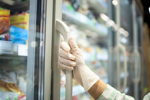Schließen sie herauf ansicht der hand in den schutzgummihandschuhen, die kühlschrank mit tiefkühlkost im supermarkt öffnen