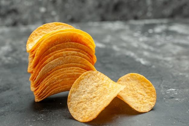 Schließen sie herauf ansicht der hausgemachten gestapelten kartoffelchips auf grauem tisch