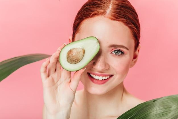 Schließen sie herauf ansicht der herrlichen ingwerfrau mit avocado. studioaufnahme des aufgeregten kaukasischen mädchens mit gesundem essen lokalisiert auf rosa hintergrund.