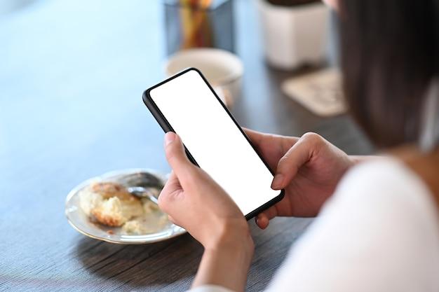 Schließen sie herauf ansicht der jungen frau, die im café sitzt und smartphone mit weißem bildschirm hält.