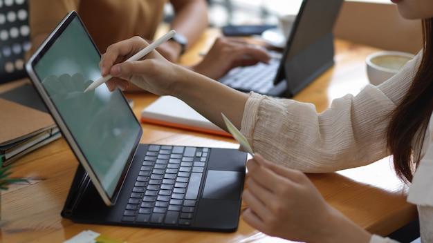 Schließen sie herauf ansicht der jungen geschäftsfrau, die mit tablette im büroraum arbeitet