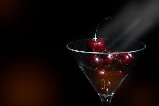Schließen sie herauf ansicht der kirsche in einem martini-glas im schwarzen hintergrund mit aufflackern und vordergrund.