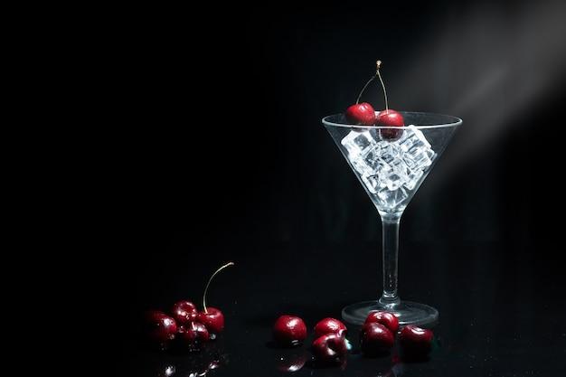 Schließen sie herauf ansicht der kirsche in einem martini-glas unter eis im schwarzen hintergrund mit aufflackern