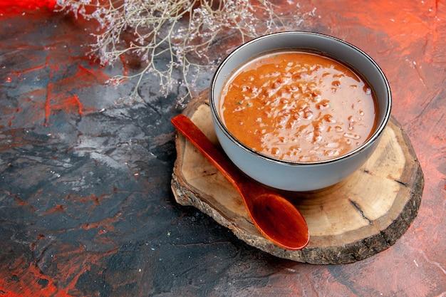 Schließen sie herauf ansicht der klassischen tomatensuppe in einem blauen schüssellöffel auf holztablett auf gemischtem farbtisch