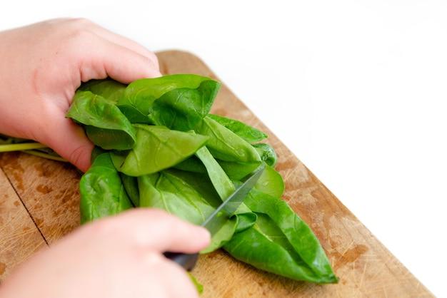 Schließen sie herauf ansicht der kochhände, die grünen spinat auf hölzernem schneidebrett schneiden.
