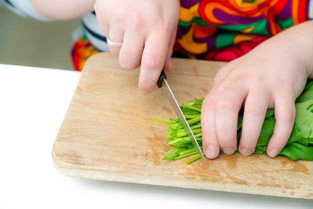 Schließen sie herauf ansicht der kochhände, die grünen spinat auf holzschneidebrett schneiden.