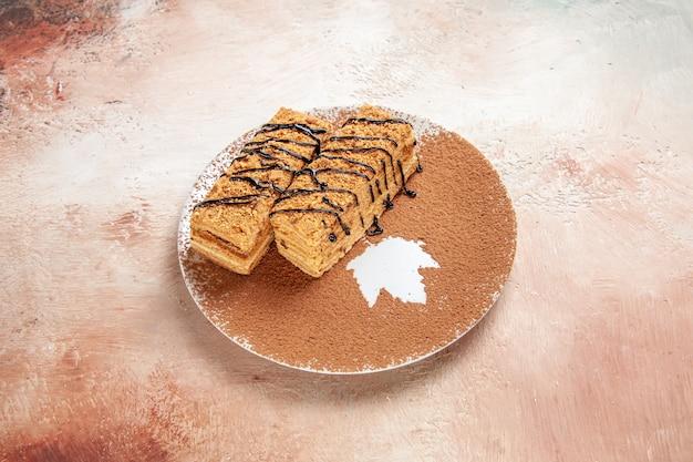 Schließen sie herauf ansicht der leckeren desserts, die mit schokoladensyrop für eine person auf buntem tisch verziert werden